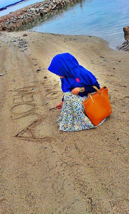 Muslimah menunggu di pasir